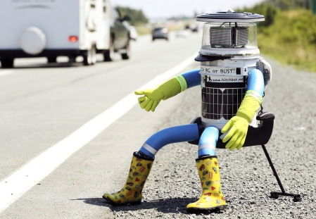 The anthropomorphic robot named hitchBOT sits on the shoulder of Highway 102 to begin its 6,000 kilometer cross-country journey outside of Halifax, Nova Scotia, on July 27, 2014. The hitch-hiking robot is part of a social experiment to see if drivers will pick up and drop off the robot in one piece to an art gallery in Victoria, British Columbia. According to the website, as of today, August 1, hitchBot has made it as far as Toronto. (Reuters/Paul Darrow)