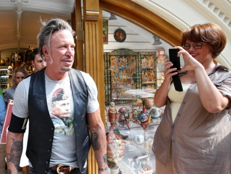 Actor Mickey Rourke wears a T-shirt with an image depicting Russia's President Vladimir Putin, as a woman looks on at GUM department store in central Moscow, August 11, 2014. (REUTERS/Maxim Zmeyev )