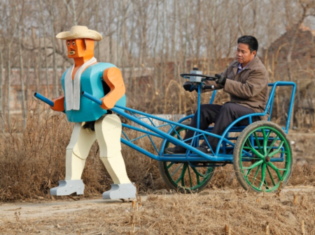 Farmer Wu Yulu drives his rickshaw pulled by a his homemade walking robot near his home in a village on the outskirts of Beijing in January 2009. This robot was made of materials found in rubbish sites. (Reinhard Krause/Reuters)