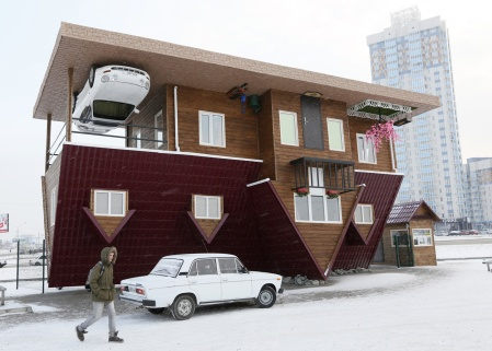 A man passes a house built upside-down in Russia's Siberian city of Krasnoyarsk on December 14, 2014. The house was constructed as an attraction for local residents and tourists. (Reuters/Ilya Naymushin)