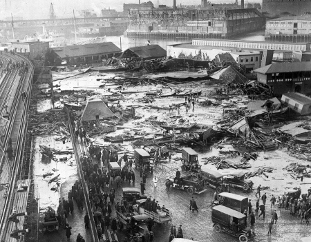 This aerial view shows the site of the molasses storage tank explosion in the section of Commercial St. between Copps Hill and the playground of North End Park in Boston, Massachusetts, on January 15, 1919. The explosion of the steel vat, ninety feet in diameter and fifty-two feet in height, caused 2.3 million gallons of molasses to flood the area, unleashing a deadly wave that rose nearly 25 feet high at one point, killing 21 people and injuring 150. The destructive flood threw people and horses about, smashed buildings, and even damaged the steel supports of an elevated railway. Rescuers had to wade through knee-deep molasses and sticky debris to reach survivors. The cause of the failure was determined to be faulty construction and poor maintenance. In the background is the Navy Yard in Charlestown.